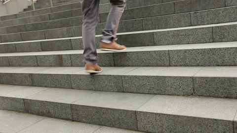 Male feet wearing sneakers running up the stairs, student walking to university Footage