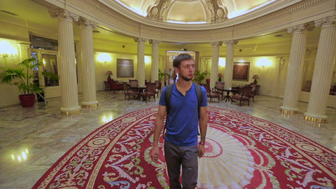 Male tourist enters lobby of magnificent hotel to read news and drink coffee Footage