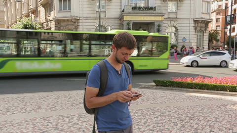 Backpacker checking public transportation schedule using app on smartphone Live Action