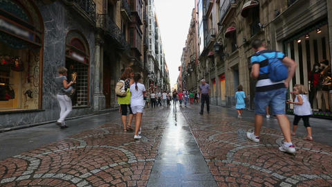 People walking on narrow streets with attractive glass shop windows in Bilbao Footage