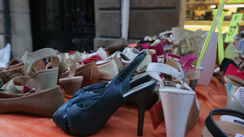 Various women's shoes on display outdoors, street vendor selling cheap goods Footage