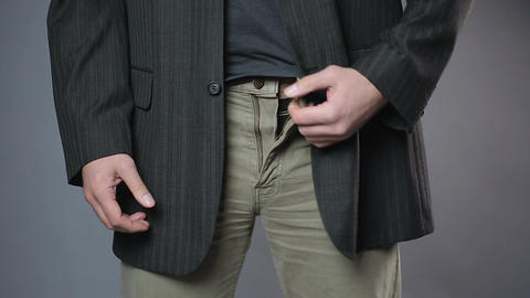 Slim man zipping and unzipping pants zipper, man's clothes, close-up shot Footage