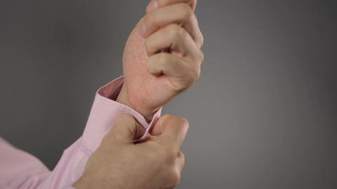 Businessman fastening button on his shirt sleeve and showing thumbs up Footage