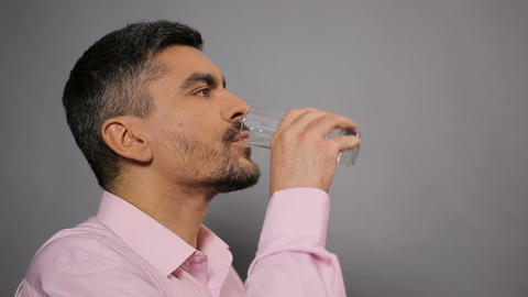 Happy man drinking tasty mineral water and showing thumbs up for camera Footage