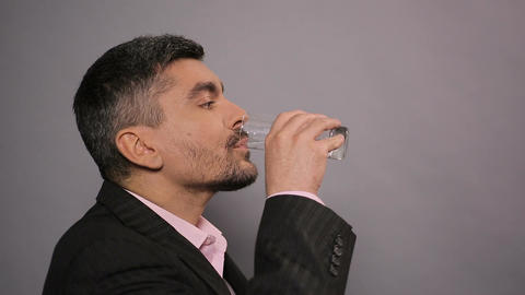 Satisfied male in suit drinking mineral water from glass and showing thumbs up Footage