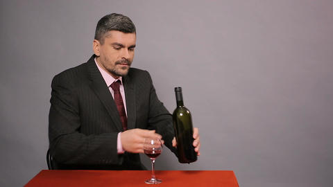 Disappointed man in black suit tasting cheap red wine, displeased winemaker Footage