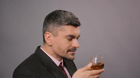 Pleased man enjoying perfect aroma and taste of whiskey, strong drink, alcohol Footage