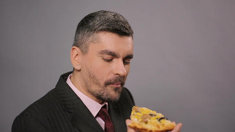 Happy male in suit eating a piece of tasty pizza at work, fat unhealthy food Live Action
