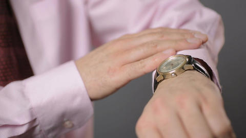 Nervous office worker checking time repeatedly on his watch. Fear of being late Footage