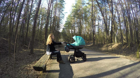 mother sit bench with baby buggy. Motherhood, child concept. 4K Footage
