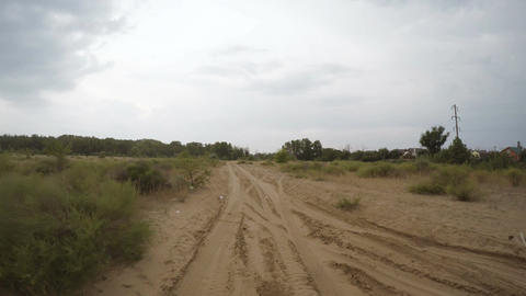 Rear view of car driving along a rural dirt road Image