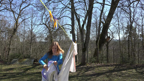 Girl hang laundry on clothesline string on forest background. 4K Footage