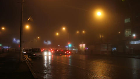 Street lights of city in fog and cars on road Footage