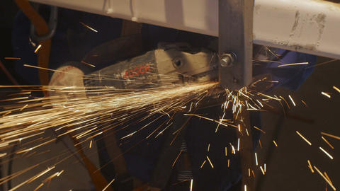 Professional Worker Grinds Metal Detail with Bright Sparks Footage