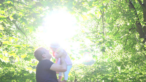 baby with father enjoying a sunny day Sunlight through leaves . 4K Footage