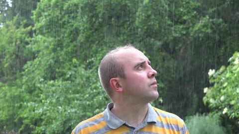 Sad worried man under heavy rain. 4K Footage