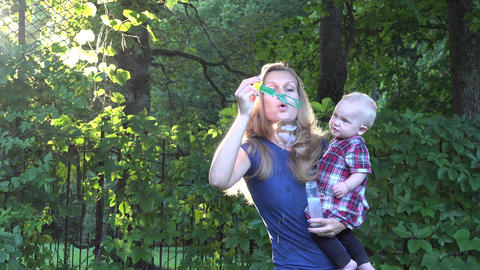 Pretty blond woman blowing soap bubbles and beautiful baby child enjoy it in bri Footage