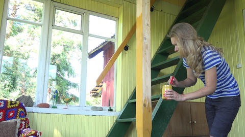 Female peasant girl painting wooden column yellow with brush in front of garden  Footage