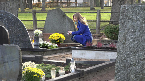 woman put candle on grave after husband father loss in cemetery. 4K Live Action