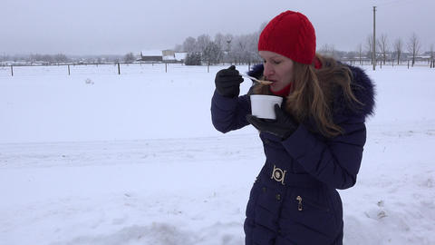 woman with red cap eat hot soup outdoor at cold winter time. 4K Footage