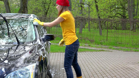 Pretty woman in colorful clothes washing black automobile car with soapy sponge Footage
