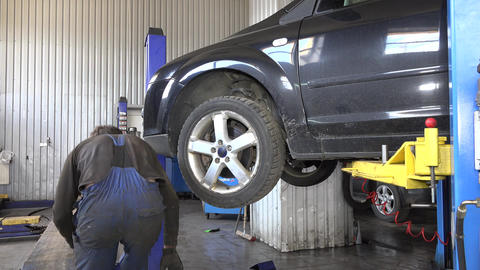 Auto mechanic removing wheel from car Footage