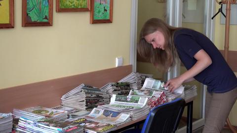 Postman woman sorting daily newspapers at work Footage