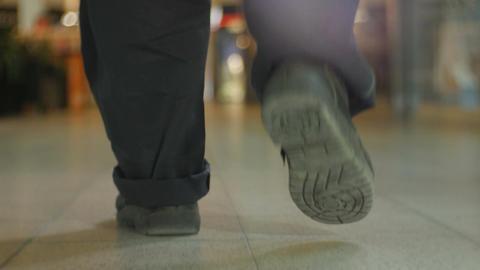 Closeup Backside View Man Walks along Bright Lit Shop Footage