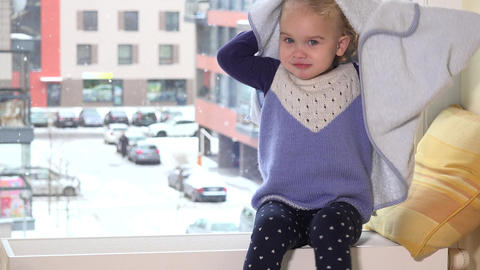Playful girl with towel on her hair sitting on radiator near window. Snowstorm Footage