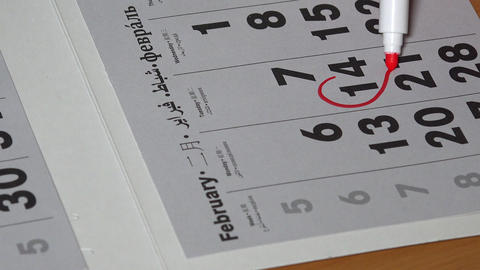 Woman hand with red marker draw a heart shape in the calendar february 14th Footage