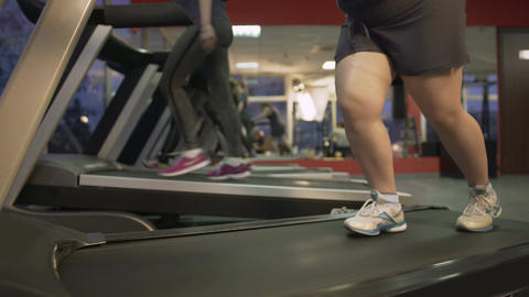 Unhealthy fat woman barely walking on treadmill, working hard to lose weight Live Action