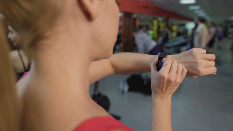 Sportive woman switching fitness tracker bracelet before active workout in gym Live Action