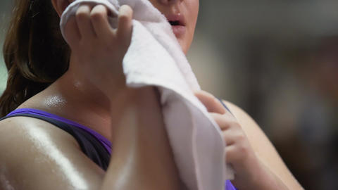 Woman wiping sweat with towel, tired after active exercising in gym, weightloss Footage