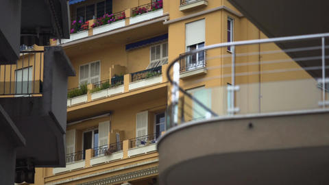 Windows of multistorey block of flats in European city, balconies with flowers Footage