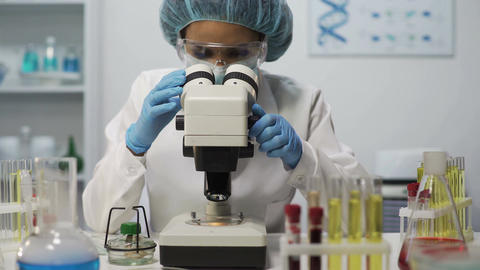 Woman in medical form working in laboratory, viewing bacteria on microscope Footage