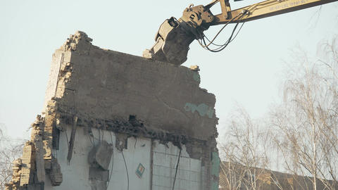 Powerful excavator devastating remains of old ruined building, wall collapse Footage