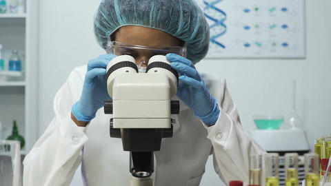 Medical analyst zooming on microscope while doing DNA analysis, medical test Footage