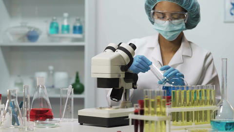 Biracial lab assistant working in laboratory, doing medical test, research Footage