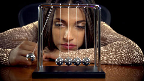 Woman Playing With A Newton's Cradle Footage