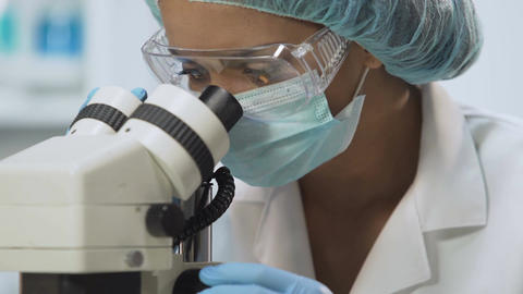 Laboratory technician using microscope for microbiological analysis, medicine Footage