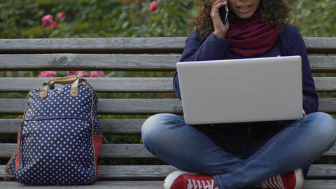 Smiling biracial woman sitting on bench, holding laptop and talking on cellphone Footage
