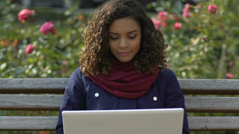 Cheerful multiracial girl making video call on laptop, talking with friends Footage