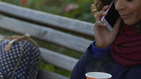 Multiracial woman holding hot tea and talking on phone outdoors, conversation Footage