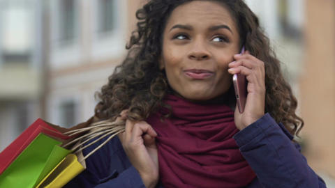 Happy mixed-race woman talking on smartphone and holding colorful shopping bags Footage