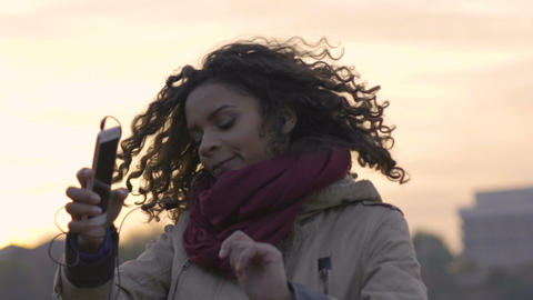 Young mixed race woman enjoying new music playlist on her smartphone at sunset Footage
