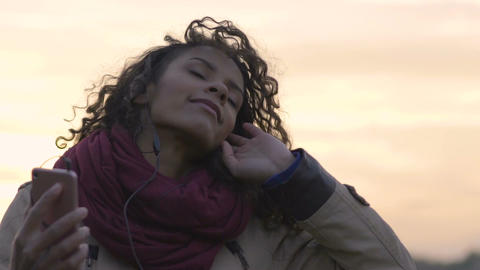 Attractive mixed race woman listening to music, dancing in trance at sunset Footage