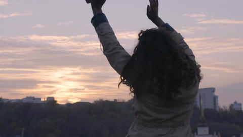 Young free happy woman dancing on background of urban landscape at sunset Footage