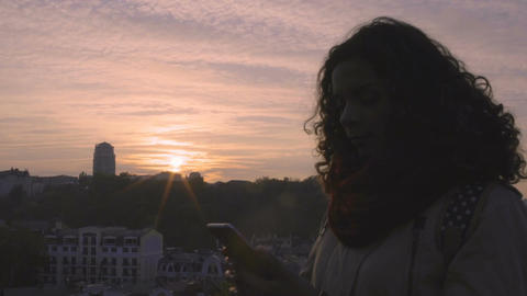 Silhouette of young happy woman texting on smartphone at sunset, relationship Footage