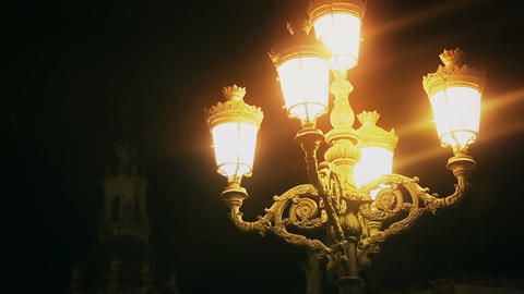 Misty medieval street lamp lighting dark night street, mysterious atmosphere Archivo