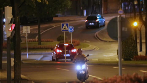 Man riding motorcycle at night, quick meal delivery service in big city, comfort Footage